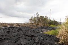 Linea elettrica ad alta tensione distrutta tramite un flusso di lava in Hawai Immagine Stock Libera da Diritti