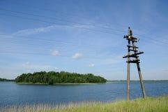 Linea elettrica ad alta tensione lungo la costa del lago Immagine Stock