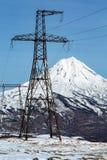 Linea elettrica ad alta tensione in montagna su fondo del vulcano snowcapped Immagine Stock