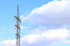 Linea elettrica contro il cielo blu con il cavo della centrale elettrica delle nuvole fotografia stock