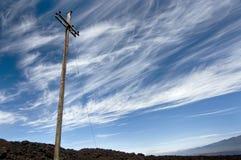Linea elettrica contro il cielo vibrante sul vulcano. immagini stock