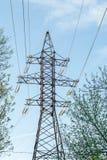 Linea elettrica della trasmissione di elettricità sul fondo del cielo blu Torre elettrica ad alta tensione fra gli alberi Fotografia Stock Libera da Diritti