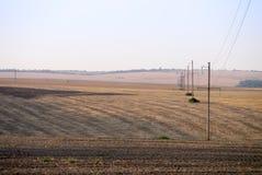 Linea elettrica di alto potere in un campo dopo un raccolto a penombra Fotografia Stock