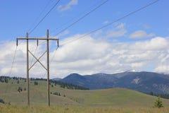 Linea elettrica in fianco di una montagna rurale Fotografia Stock