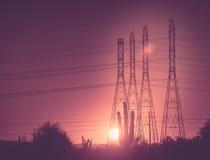 Linea elettrica pali al tramonto immagini stock