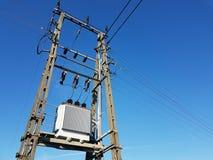Linea elettrica posta contro un cielo blu con una traccia da un jet Costruzione di calcestruzzo con i nastri metallici La trasmis Fotografie Stock