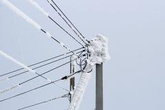 Linea elettrica su un palo di molti cavi coperti di strato spesso di neve fotografie stock