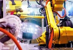 Linea industriale con i robot gialli sui lati, sulla produzione e sull'elaborazione delle parti di metallo, fuoco slective fotografia stock libera da diritti