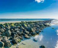 Linea retta delle rocce impilate sulla spiaggia con una vista di oceano immagine stock libera da diritti