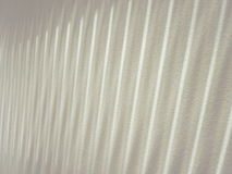 Linear light pattern from vertical blinds. Light shining through vertical blinds against gritty off white wall Royalty Free Stock Image