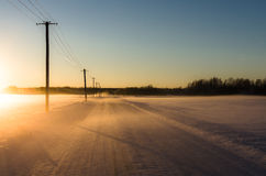 Linear Perspective of telephone poles lining a snowy road in a wintry landscape Royalty Free Stock Image