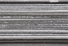 Linear texture of gray asbestos slate plates stacked on top of each other close-up side view Royalty Free Stock Images