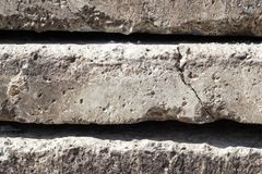 Linear texture of gray concrete slabs with a crack stacked on top of each other close-up side view. Conceptual or metaphor wall royalty free stock photography