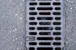 Lineares Gitter des Grabenabflusses auf Straße Stockbild
