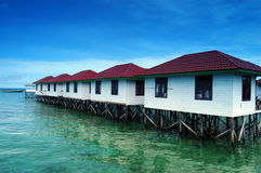Lined lodging buildings on the beach. Lined lodging buildings are made of wooden planks built over the sea on the beach Royalty Free Stock Image
