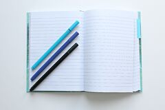 Lined notebook open with three pens Stock Image