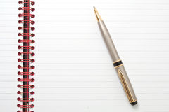 Lined notepad with red binding and a pen Royalty Free Stock Photos