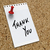 Lined notepaper with thank you note. Lined notepaper with thank you message with red pushpin on corkboard Stock Photo