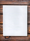Lined paper on dark table Stock Images
