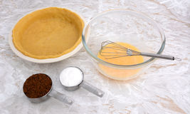 Lined pie dish, beaten egg and measuring cups of sugar Royalty Free Stock Image