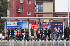 Lined up people at bus stop, Dalian, China. DALIAN-NOV. 11, 2012. Bus-stop with advertising on Nov. 11, 2012 in Dalian. China has 50,000 outdoor advertising Stock Photo