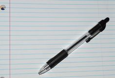 Lined white notebook paper with a black pen Royalty Free Stock Photo