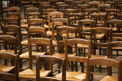 Lined Wooden Chairs. Standing like soldiers at attention, these wooden chairs are awaiting for the next crowd of people to make use of them Stock Image