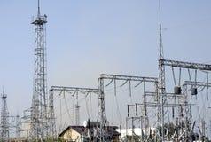 Linee ad alta tensione contro lo sfondo delle stazioni di distribuzione elettrica ad alba Fotografia Stock Libera da Diritti