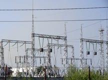 Linee ad alta tensione contro lo sfondo delle stazioni di distribuzione elettrica ad alba Fotografia Stock