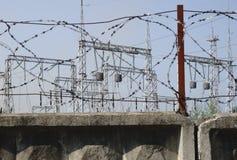 Linee ad alta tensione contro lo sfondo delle stazioni di distribuzione elettrica ad alba Fotografie Stock