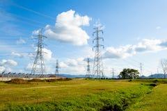 Linee ad alta tensione e piloni di potere in un agricult piano e verde immagine stock