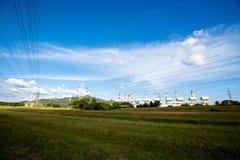 Linee ad alta tensione e piloni di potere in un agricult piano e verde fotografia stock libera da diritti