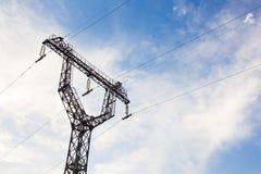 Linee ad alta tensione e piloni di potere un giorno soleggiato con le nuvole nel cielo blu Fotografia Stock