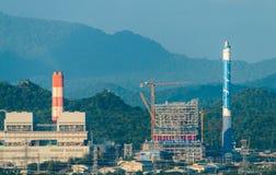 Linee ad alta tensione e piloni di potere in un paesaggio agricolo piano e verde con i cirri su cielo blu Fotografia Stock