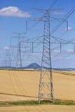 Linee ad alta tensione e piloni di potere in un paesaggio agricolo verde un giorno soleggiato con i cirri nel cielo blu Fotografia Stock