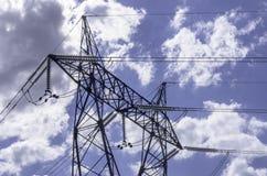Linee ad alta tensione sotto il cielo nuvoloso blu Fotografia Stock Libera da Diritti