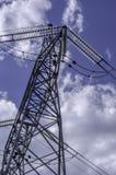 Linee ad alta tensione sotto il cielo nuvoloso blu Fotografia Stock