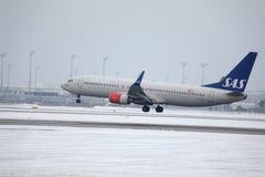 Linee aeree scandinave Boeing di SRS 737-800 LN-RRJ nell'aeroporto di Monaco di Baviera, neve Fotografie Stock Libere da Diritti