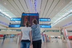 Linee aeree terminali di informazioni di volo delle ragazze dell'aeroporto Immagine Stock