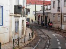 Linee del tram in via stretta di Lisbona Fotografia Stock