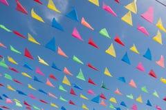 Linee di bandiere colorate davanti a cielo blu Fotografia Stock