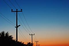 Linee di energia elettrica contro un cielo di alba Immagine Stock