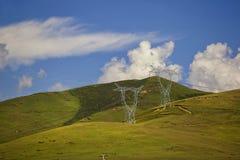 Linee di linee elettriche sulle colline verdi Fotografia Stock