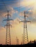 Linee elettriche ad alta tensione al tramonto Stazione di distribuzione di elettricità Torre elettrica ad alta tensione della tra Fotografia Stock Libera da Diritti