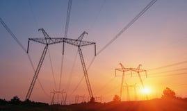 Linee elettriche ad alta tensione al tramonto Stazione di distribuzione di elettricità Immagini Stock Libere da Diritti