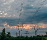 Linee elettriche ad alta tensione al tramonto Stazione di distribuzione di elettricità Torre elettrica ad alta tensione della tra Immagine Stock