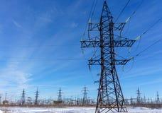 Linee elettriche ad alta tensione a cielo blu Stazione di distribuzione di elettricità Fotografie Stock Libere da Diritti