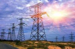 Linee elettriche ad alta tensione contro il cielo con il sole Fotografie Stock Libere da Diritti