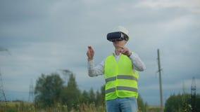 Linee elettriche ad alta tensione controllate da un ingegnere maschio facendo uso di realtà virtuale per controllare potere Energ video d archivio
