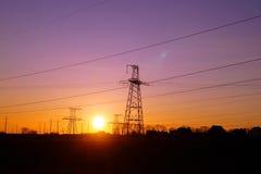 Linee elettriche ad alta tensione di distribuzione pilone al tramonto Fotografie Stock Libere da Diritti